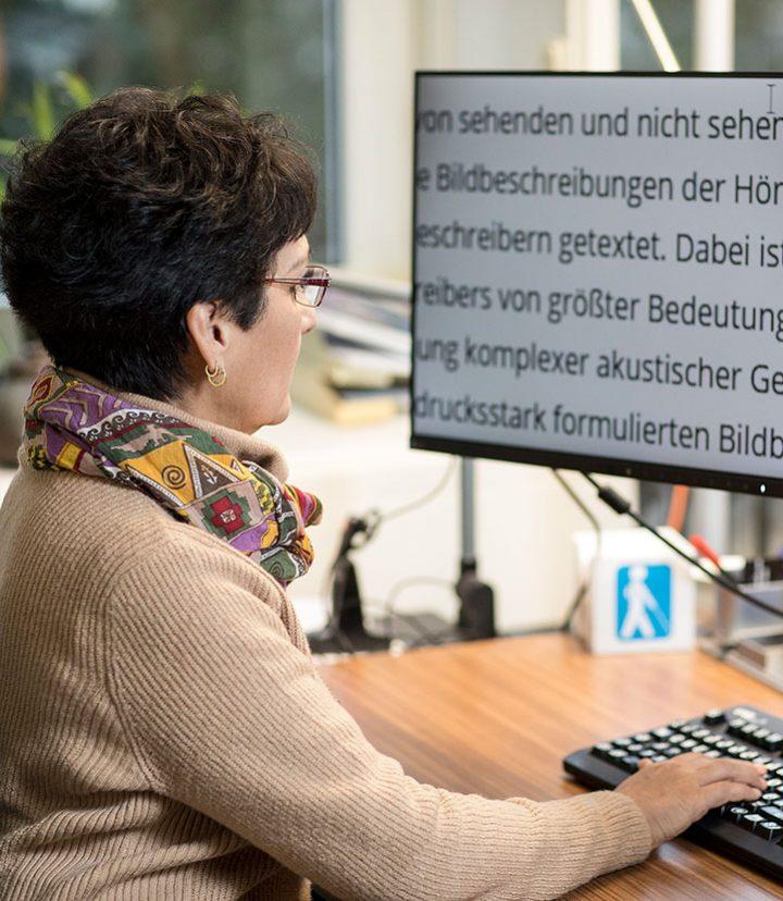 Frau arbeitet an einem Bildschirm mit großer Schrift