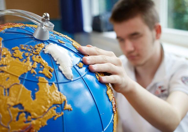 Jugendlicher ertastet Globus