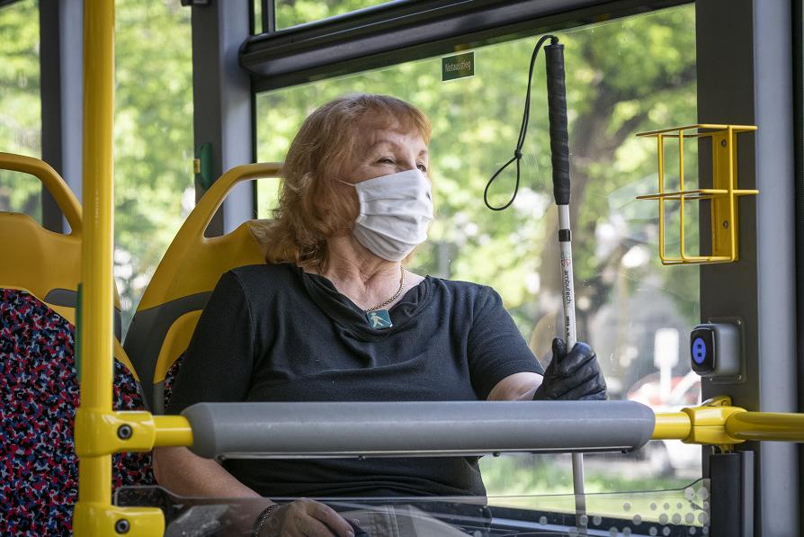 Sehbehinderte Frau mit Maske und Blindenführstock im Bus