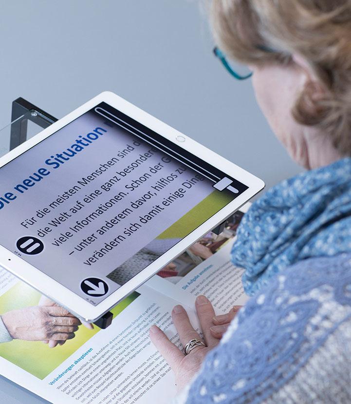 Frau mit elektronischer Lesehilfe